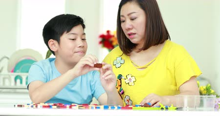 blocos : Happy asian family mother and son playing plastic block together . Stock Footage