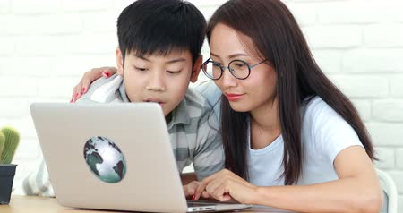 be sad : Asian mother and son be bored with learning and reading education from laptop computer.
