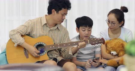 acoustic : Happy asian Father playing guitar for his family at home Stock Footage