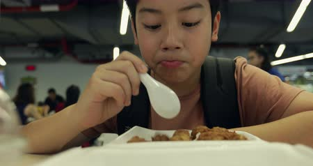 nugget : Little asian boy eating meat ball with rice at canteen dining hall. Little asian child eating fried rice with meat ball.