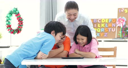 recess : Asian teacher and Three kids entertaining themselves using digital tab and laughing