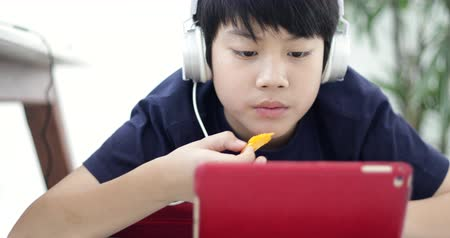 tab : Boy relaxation on long chair and looks at cartoons on tablet and eat potato chip at home. Stock Footage