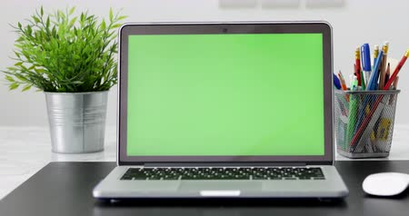em branco : A laptop computer with a key green screen set on work office table. Vídeos