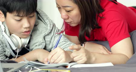 encouraging : Asian mother helps his young son while the boy is doing his homework at home.