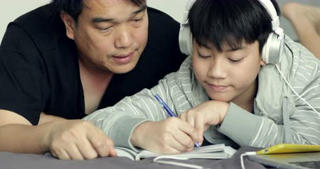 school children : Asian Father and son doing homework on the table in the living room .