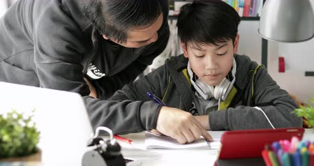 his : Asian Father and son doing homework on the table in the living room .