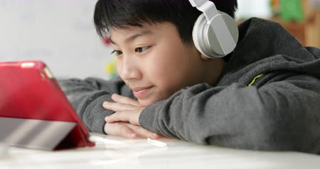 education kids : Young asian boy playing on tablet computer with headphone at home, Dolly in. Stock Footage