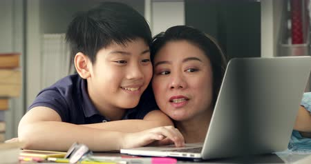 домашнее задание : Cute asian mother helping your son doing your homework at home with smile face together.