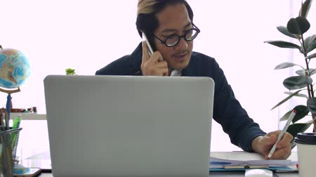 Businessman in office  using laptop and cell phone, 4K Slow motion of office man talking and typing on mobile phone