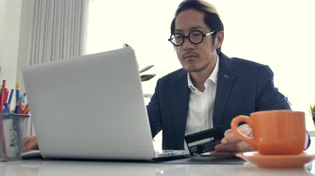 Businessman working on laptop computer with credit card in the office, 4K Slow motion asian business man wearing eyeglass in office. Stok Video