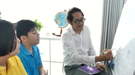 Tutor room children in class writing on board with teacher. 4K Slow motion Asian child learning with teacher at home. Stok Video