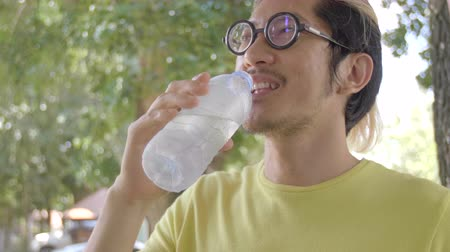 Slow motion 4K of asian sportsman drinks water from bottle .