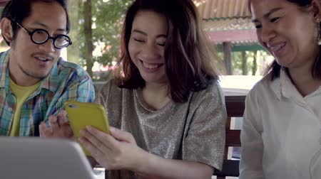 Beautiful asian Woman Shows Interesting Stuff on Her Smartphone to Her Friends while They Have Good Time in garden They Laugh, Joke