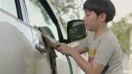 4K Slow motion of asian cute boy wash a car with smile face.