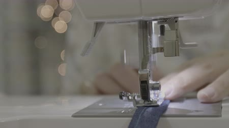 Close up footage of a woman sewing a apron with a sewing machine