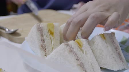 Woman made sandwiches and putting them into the plate.