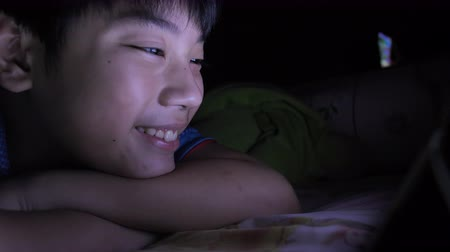 Young asian boy playing with a cell phone or smartphone on a bed. night
