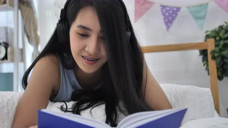 Slow motion, 4K of Beautiful Asian girl resting on bed at the bed Room While Reading a book and looking at a camera with smile face