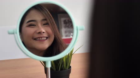 Slow motion of young and fresh asian cute girl smiles happily, Beauty makeup woman smile and look mirror.