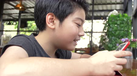 Slow motion of Young asian boy playing with a cell phone or smartphone at cafe with smile face . Stok Video