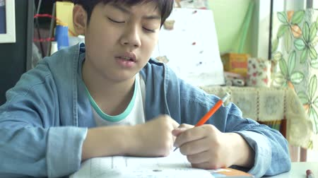 Slow motion of Happy asian boy doing your homework with smile face. 4K Stock Footage