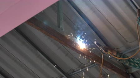 сварщик : Workers weld steel structure with Electric welding machines in factory, Slow motion of hand weld steel repair of roof .