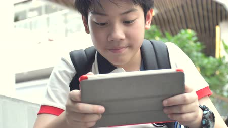 risonho : Asian boy playing on tablet computer with smiley face, Slow motion of thailand boy watching on tablet and relaxing.