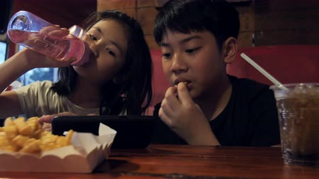 картофель фри : Happy asian child watching on mobile phone and enjoy eating potato fires, Slow motion of brother and sister at restaurant.