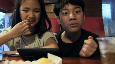 картофель фри : Happy asian child watching on mobile phone and enjoy eating potato fries, Slow motion of brother and sister at restaurant. Стоковые видеозаписи
