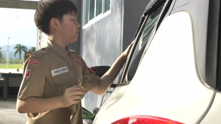 scout : Asian boy in boy scouts uniform car washing at home, Thailand boy scouts helping your family at home. Stock Footage