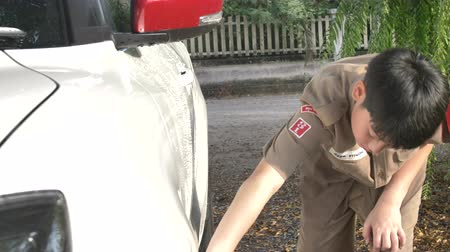 harcerz : Asian boy in boy scouts uniform car washing at home, Thailand boy scouts helping your family at home. Wideo