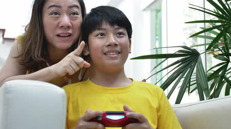 papai : Asian mother and son playing video game at home together.4K Slow motion of happy family playing with smile face.