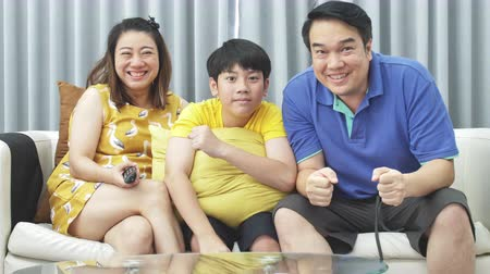 family watching tv : Slow motion of asian family father mother and son on couch, Looking at camera  with smile face.