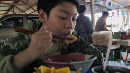ramen : Slow motion of Young asian boy eating noodle by chopstick at restaurant.