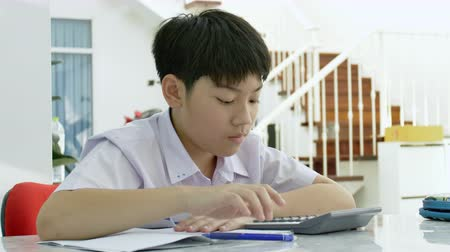 учитель : Slow motion of Asian mother helping her son doing homework on white table.  Serious Asian mother with son doing homework in the living room. Mom teaches son how to genius. Стоковые видеозаписи