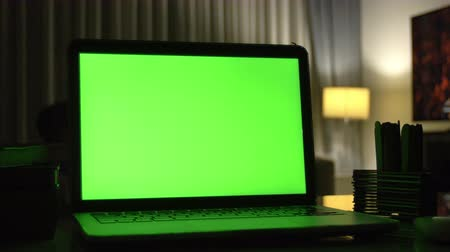 área de trabalho : Laptop with green screen. Dark home office. Dolly shot of Perfect to put your own image or video.