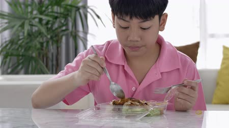 cozinha japonesa : 4K asian boy eating lunch alone at home, Food for lunch, lunchboxes with jasmine rice box. Stock Footage