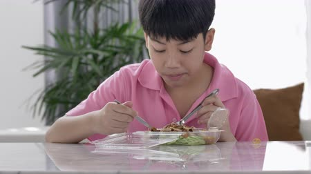 cozinha japonesa : 4K asian boy eating lunch alone at home , Food for lunch, lunchboxes with jasmine rice box. Stock Footage