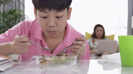упакованный : 4K asian boy eating lunch at home, Food for lunch, lunchboxes with jasmine rice box.