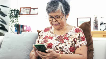 nagymama : Asian Senior woman using smart phone  at home, Happy grandmother with technology in hand .Slow motion 4K, Dolly shot. Stock mozgókép