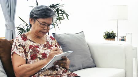 remember : Asian ponder senior woman thinking and writing something. Old woman weaken remembrance with serious face at home.