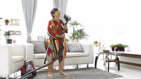 vácuo : Asian Senior woman vacuuming floor at home. Dancing and singing with smile face. 4K Slow motion Vídeos