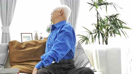 osteoarthritis : Asian Senior man with white mustache using tablet computer at home, Happy grandfather with technology in hand .Slow motion 4K, Dolly shot.