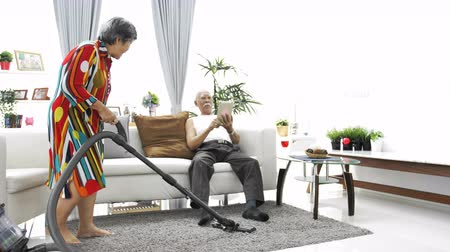 vácuo : Happy asian senior man playing tablet computer and Senior woman vacuuming floor at home. 4K slow motion Vídeos