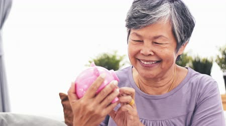 копилку : Cheerful asian senior woman shaking piggy bank smiling at camera. Portrait of mature woman saving money holding up piggy bank indoors. 4k