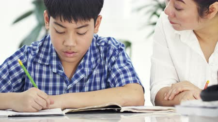 education kids : Young asian mother teaching son at home. Asian mother with son doing homework on table with smile face. Dolly shot 4K Stock Footage