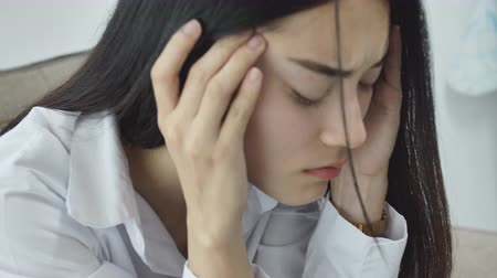 fájó : Asian woman feeling stress from work in the office.Tired business woman at workplace in office holding his head on hands feel headache. Stock mozgókép
