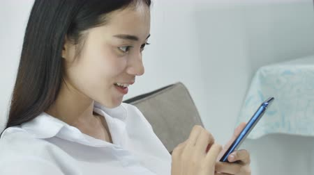 download : Beautiful mature asian woman writing a text on smart phone. Smiling woman feeling happy on reading a message on smartphone. Relaxed woman checking email and typing on cellphone at office. Vídeos
