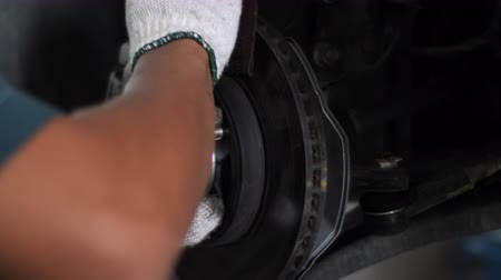 alineación : Auto mechanic working on brakes in a car repair shop domestic garage. Professional repair of a car. Archivo de Video