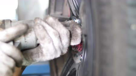 подвесной : Auto mechanic working on brakes in a car repair shop domestic garage. Professional repair of a car. Стоковые видеозаписи